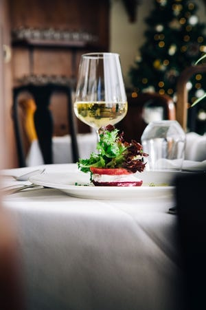 A beet and goat cheese appetizer, on a white tablecloth with a glass of wine, creates a sparkling picture for a small Thanksgiving meal.