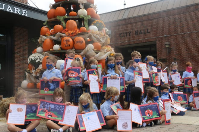 Kindergarteners from Battle Ground Academy show their artwork for Paint the Town Orange on Oct. 12.