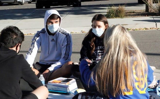 Tiffany Lovato y Ethan Bevers hablan con sus compañeros de clase, el lunes 12 de octubre de 2020, mientras protestan contra las órdenes de salud pública que les prohíben asistir a clases en persona o competir en deportes en Bloomfield High School.