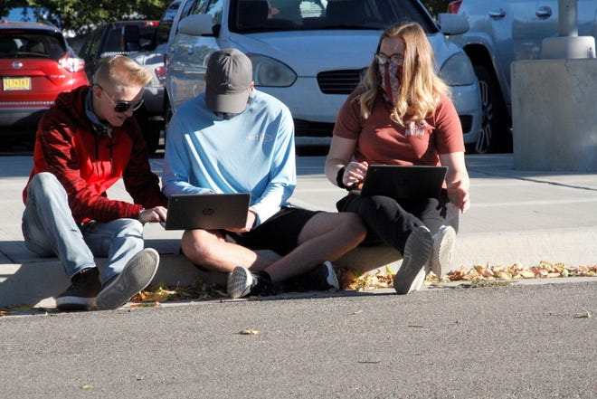 A trio of Bloomfield High School students work on classwork, Monday, Oct. 12, 2020, while protesting the state public health orders that prevent them from attending class in person or participating in sports. The group was part of a protest at the high school.