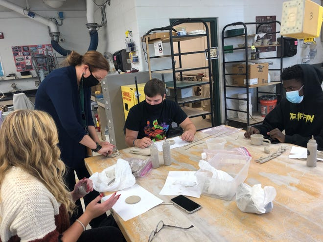 Erin Harbar, Novi High School art teacher, assists Cameron Bloom while Riley MacDonald (left) and Devin Lacy watch during ceramics class on Oct 8, 2020.