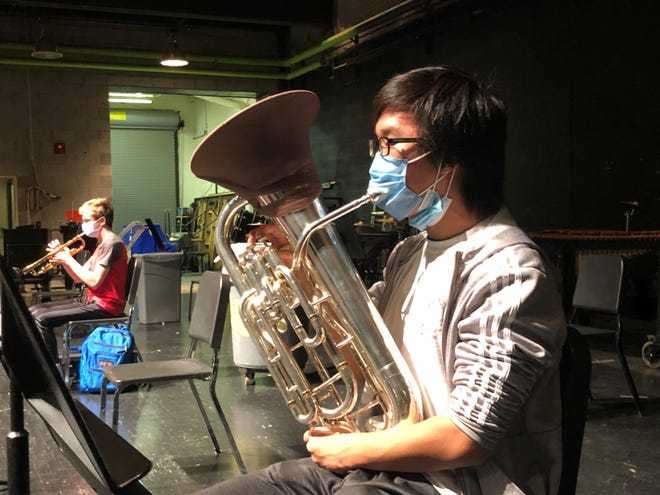 Daniel Lee, a Novi High School junior, plays baritone euphonium while wearing a modified mask and socially distanced during band class on Oct. 8, 2020. Mandatory masks will be back for the start of the 2021-22 school year, but social distancing will be less with about 95% of students returning to 5 days per week in-person learning.