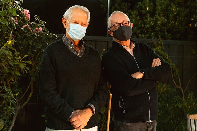 In this Monday, Oct. 12, 2020, photo provided by Stanford University, Robert Wilson, left, and Paul Milgrom wear masks as they stand for a photo in Stanford, Calif. The two American economists, both professors at Stanford, won the Nobel Prize in Economics for improving how auctions work. That research that underlies much of today's economy — from the way Google sells advertising to the way telecoms companies acquire airwaves from the government.
