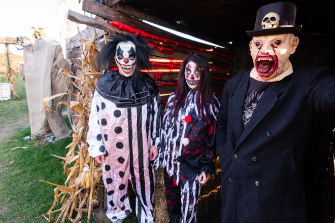 From left, Ethyn Blair, Sarah Terpening and Ben Tarzwell wait in-costume at the entrance to the haunted house at Haunted Orchard of Deimos Friday, Oct. 9, 2020, at McCallum's Orchard & Cider Mill.