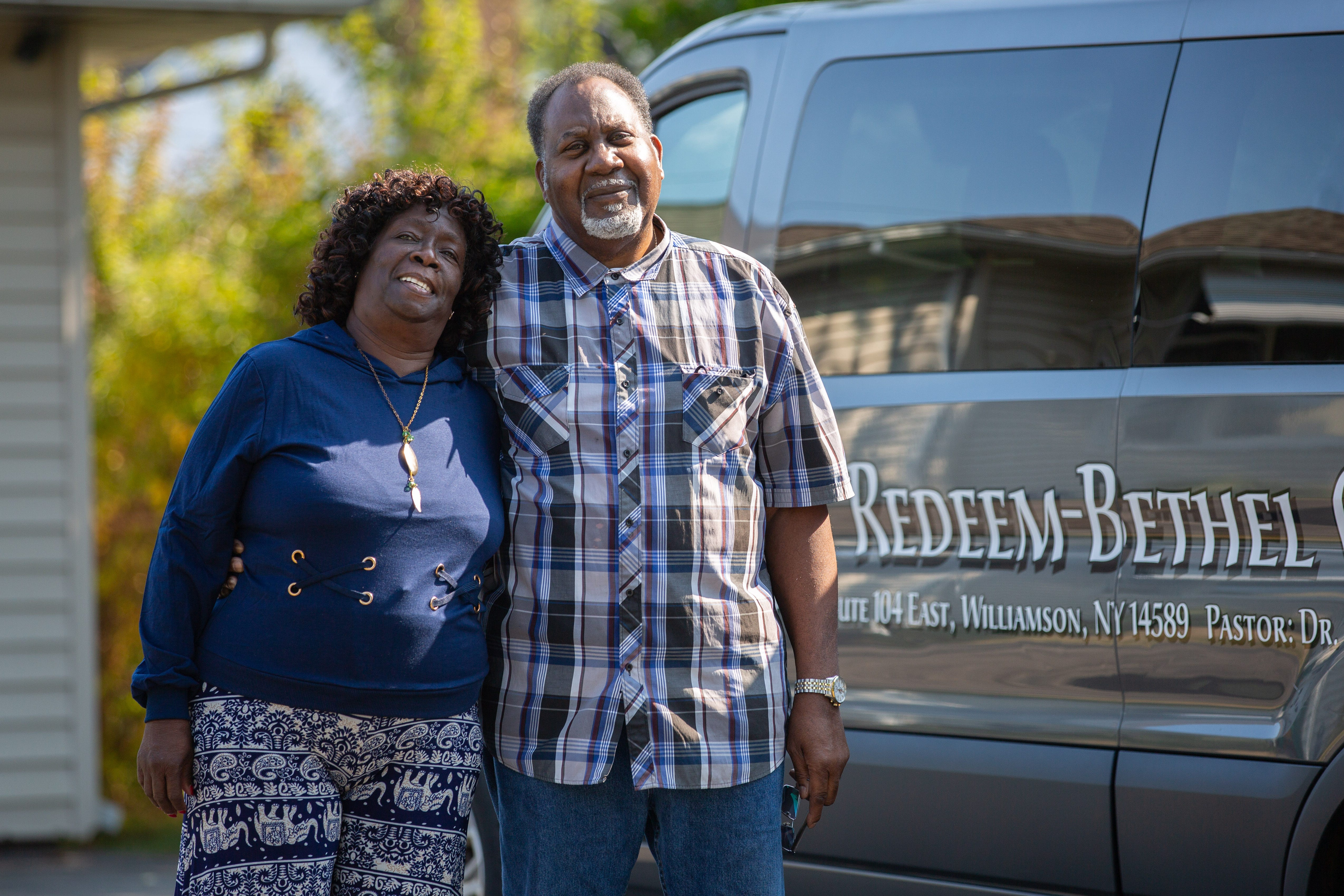Roberta Carter and her husband, James, stand beside their church's van parked in their driveway.
