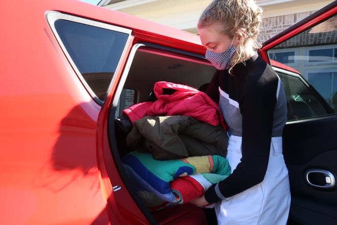 Volunteer Anya Bryne unloads coasts and blankets donated to the Big Bend Homeless Coalition's annual event to help homeless families and veterans.