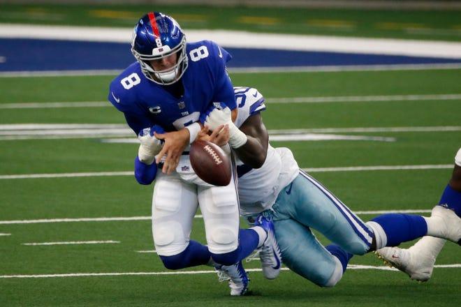 El mariscal de campo de los New York Giants, Daniel Jones (8), suelta el balón cuando es capturado por el ala defensiva de los Dallas Cowboys, DeMarcus Lawrence (90), en la primera mitad de un juego de fútbol americano de la NFL en Arlington, Texas, el domingo 11 de octubre de 2020 (AP Photo). Por Michael Ainsworth)