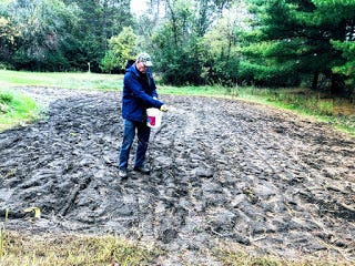 Apps' son Steve sowing winter rye on the garden.
