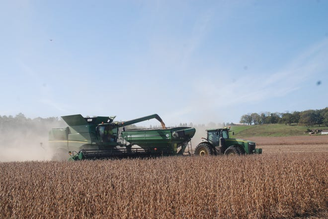 A blue sky provides a perfect backdrop for a combine and grain cart moving across a field in southern Wisconsin where a group of farmers reached out to help bring in the harvest for a family suffering a double loss this year.