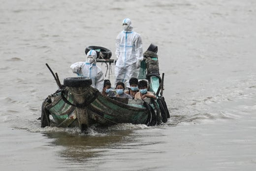 Volunteers wearing personal protective equipment (PPE) on a boat transfer people suspected of having the COVID-19 coronavirus to a quarantine center in Yangon, Myanmar on Oct. 12, 2020.
