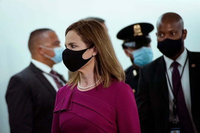 Supreme Court nominee Judge Amy Coney Barrett walks to her Senate Judiciary Committee confirmation hearing on Capitol Hill on Monday.