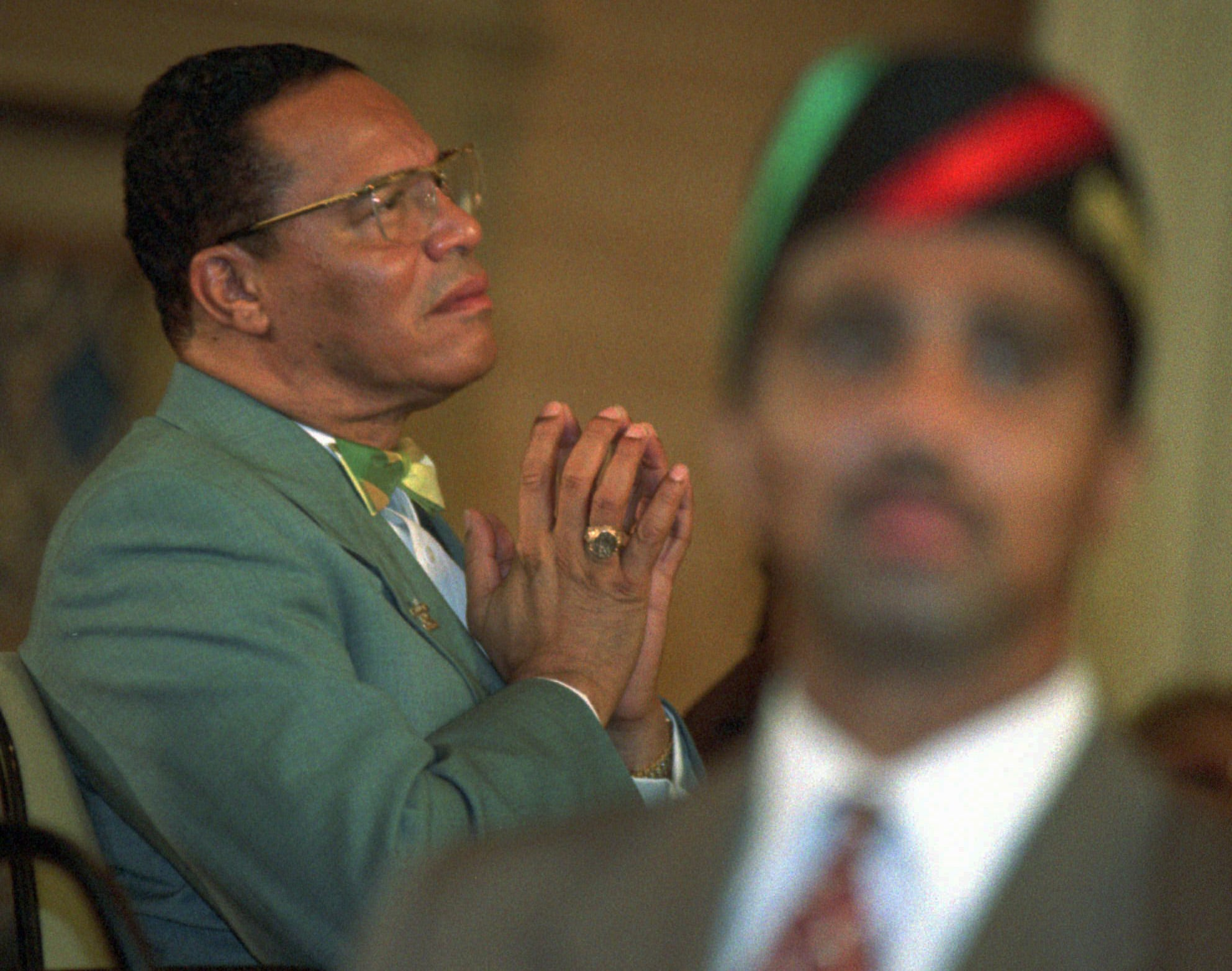 Nation of Islam leader Louis Farrakhan has a quiet moment during a rally at Operation PUSH headuarters in Chicago on Oct. 14, 1995, two days before the Million Man March he organized in Washington, D.C. One of his bodyguards is in the foreground.