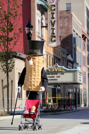 Rickshaw Willie, dressed in a Mr. Peanut costume, walks along South Main Street on Tuesday to alert people that the Peanut Shoppe has reopened in downtown Akron after being closed for seven months.