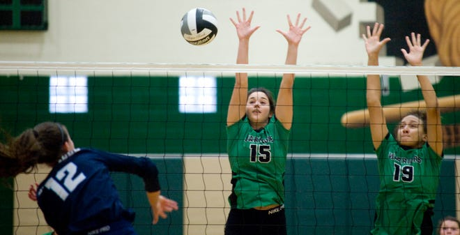West Branch's Alexa Gossett (15) and Mikalyn Fitts jump to block a shot at the net in a match against Louisville at the West Branch Field House Monday, October 12, 2020.