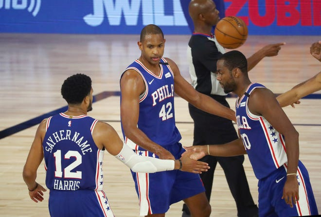 Al Horford, 42, celebrates with teammates Tobias Harris, 12, and Alec Burks during the Sixers' playoff loss to the Celtics.