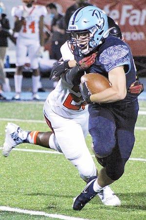 Bartlesville High School senior tailback Dylan McCoy attempts to shed a tackler.