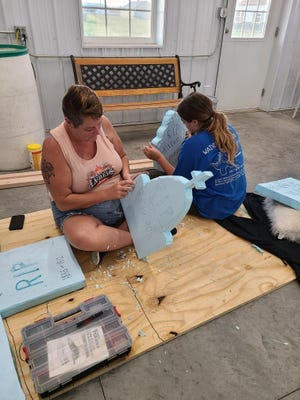 Melinda Anderson and Autumn Brown work on props for the attraction.