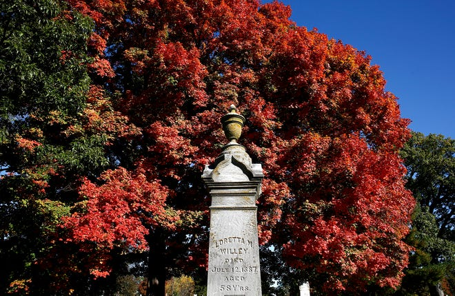 A monument at Green Lawn Cemetery is highlighted by red leaves on Tuesday, October 13, 2020.