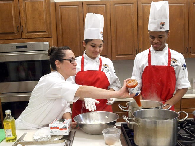 Nicholls State graduate Meg Bickford (left) works with students Jessica Arceneaux and Austin Babineaux during an Empowered Women's Chef Series lecture in Sept. 14, 2016, at the Thibodaux university's Chef John Folse Culinary Institute.