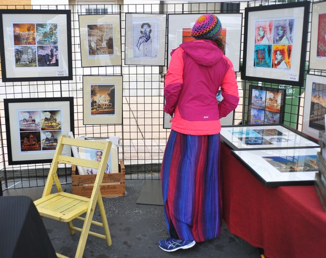 Kelly Ann Reagan looks at Steven Hlavac's photography art on at the Leesburg Fine Arts Festival in 2018. The Leesburg Center for the Arts is hosting Art Create this weekend.