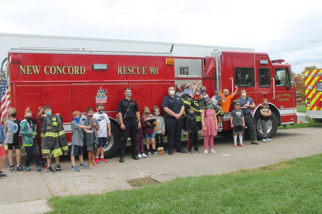 New Concord firefighters, Billy Mitchell, Ben Lumbatis,  Jacob Gaston, pose with students at Larry Miller Intermediate School on Monday during a surprise pizza party on Monday. The students won the pizza party sponsored by I am A Warrior Against Suicide for completing an act of kindness by sending letters of support to area first responders.