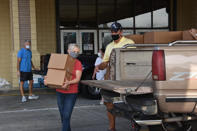 Volunteers with Catholic Charities and Second Harvest Food Bank distributed free food to hundreds of families last month at the Houma-Terrebonne Civic Center.