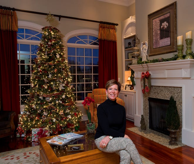 Mimi Elmore sits in her den that features her main Christmas tree, on which every ornament is individually meaningful to her.