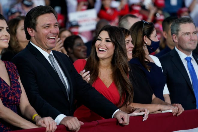 Florida Gov. Ron DeSantis smiles next to Kimberly Guilfoyle as President Donald Trump speaks during a campaign rally at Orlando Sanford International Airport, Monday, Oct. 12, 2020, in Sanford, Fla.