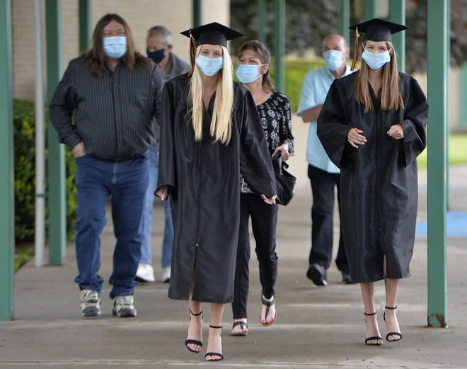 Twin sisters Taylor, left, and Paige Thomas and family members enter Harbor Creek High School for a commencement ceremony on May 29. It was the first of three days recognizing graduating seniors in a stand-in for the usual commencement ceremony.