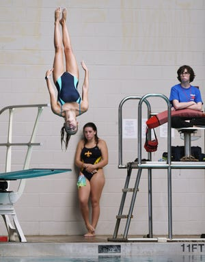 A diver launches from the board during the Gateway Conference diving championship at Cecil Aquatics Center.
