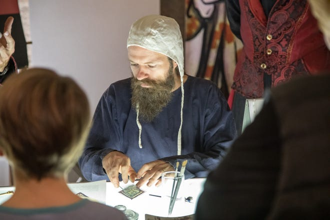 An artist demonstrates stained glass painting during the Medieval Festival held in 2019. [PHOTO COURTESY OF GLENCAIRN MUSEUM]