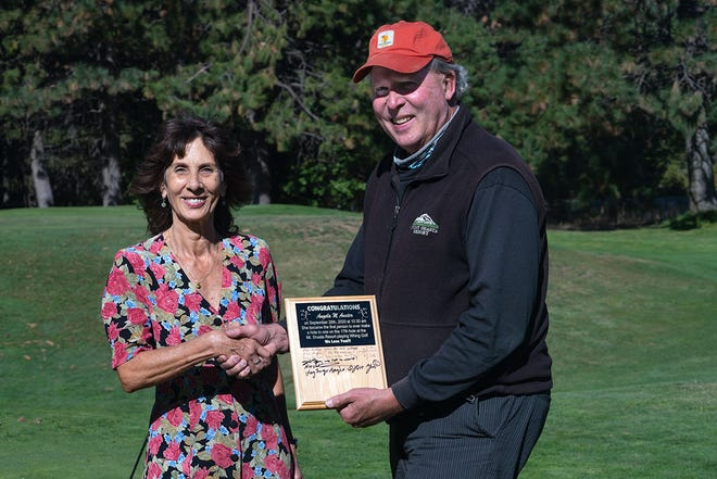 Mount Shasta's Angela Auxter is awarded a plaque after hitting a Whing hole in one on Mount Shasta Resort's 17th hole on Sept. 28. Presenting the award is John Fryer, the game's creator and one of the founders of the Mount Shasta Resort.
