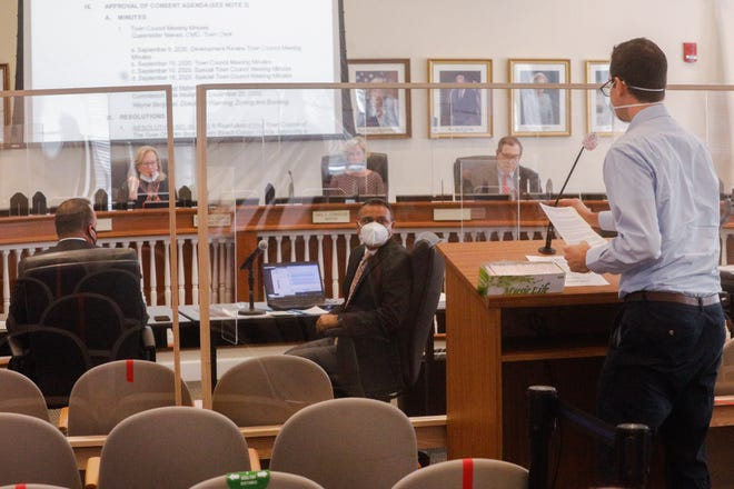 Separated by Plexiglass panels, a citizen makes remarks Tuesday to the Town Council during its first live meeting in several months.