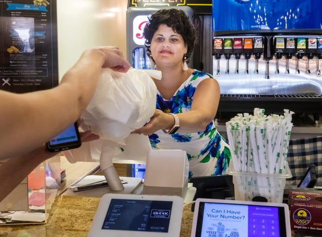 In the early, pre-mask days of the pandemic, Maria Christodoulou hands a takeout order to a customer at Your Greek Cousin, the West Palm Beach restaurant she owns with her husband.