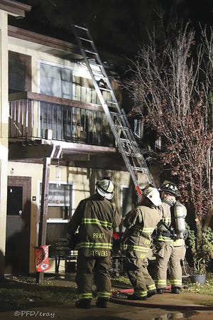 City of Pratt Fire Chiefs George Stevens and David Kramer, and firefighter Josh Stahl position a ladder at Pinewood Place Apartments during the departments response to a fire there last Tuesday.