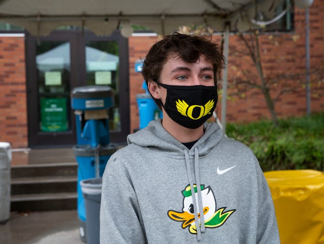 University of Oregon freshman Michael McVay from San Diego, California, waits for a ride outside the University Health Center after being tested for COVID-19.