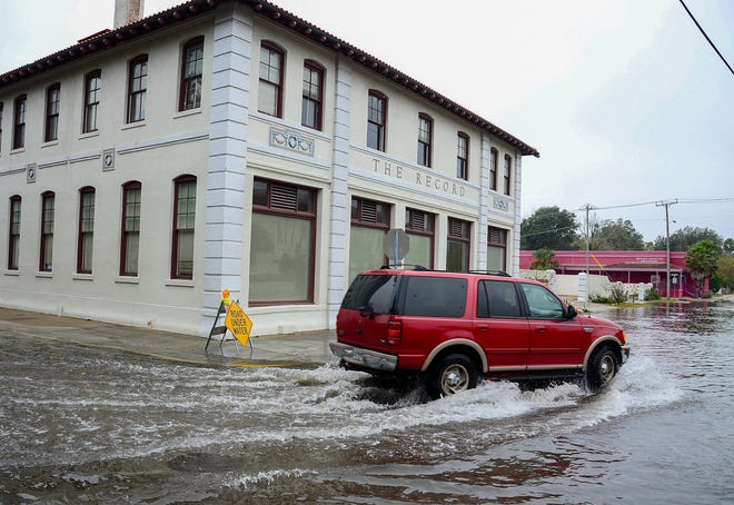 In St. Augustine, an SUV turns from a flooded Cordova Street to a flooded Bridge Street