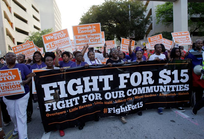In this April 15, 2015, file photo, protesters in Miami march in support of raising the minimum wage to $15 an hour. Under Amendment 2, Florida voters will decide whether to raise the minimum wage from $8.56 to $15 by 2026.