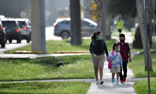 Students walk to Wilkinson Elementary in this Aug. 31 file photo, on the first day of school in Sarasota County. The School Board's current policy generally requires all students and staff to wear masks throughout the school day, with a handful of exceptions.
