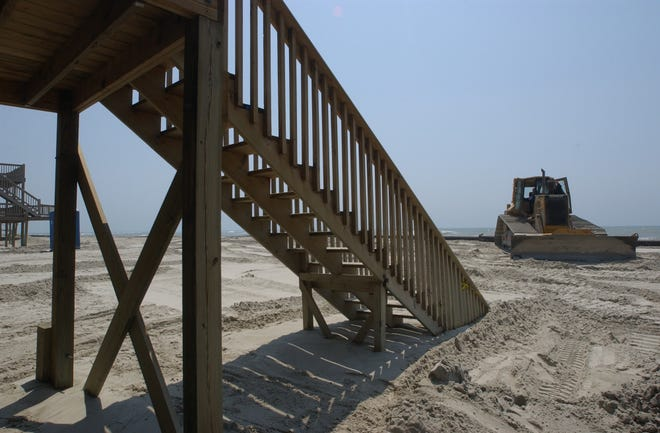 The stairs leading down to the beach from a house on the front row of North Topsail Beach at high tide on June 14th, during the beach renourishment project. The bulldozer in the background is moving sand piped in from the New River Inlet dredging project.