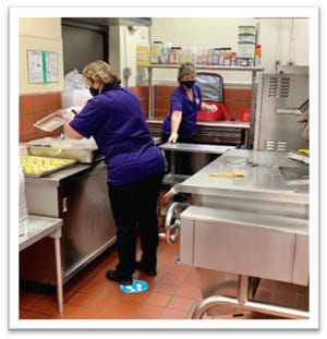 Oaks Road Academy cafeteria staff works to prepare meals while wearing masks.