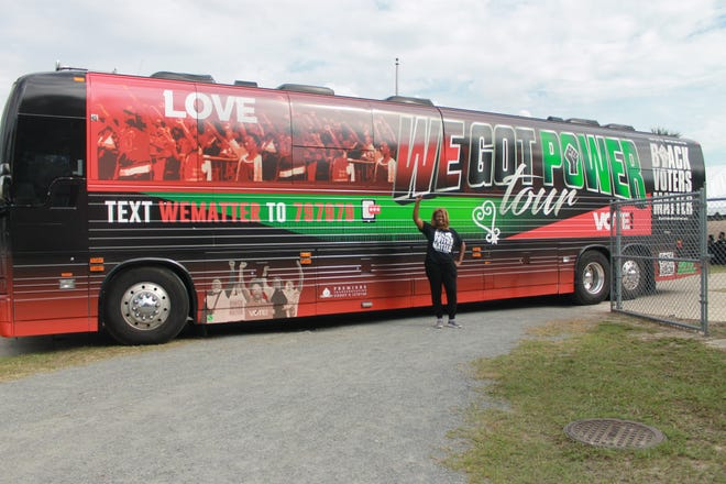 LaTosha Brown, co-founder of Black Voters Matter, stands in front of the 'We Got Power' tour bus at Citizens Field located at 1400 NE Eighth Ave. with a raised fist in the air on Saturday.