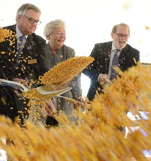 Feed flies through the air as Attalla Mayor Larry Means, Alabama Gov. Kay Ivey and Gadsden-Etowah IDA Executive Director David Hooks participate in the ceremonial ground breaking Nov. 5, 2019, for a new $55 million grain storage and distribution center in Attalla.