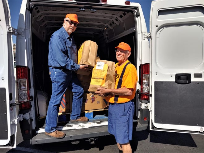 """Tony Ashworth, right, founder of the Pueblo """"Feeding the 5,000,"""" and Corry Higbee, executive director of Pueblo Cooperative Care Center, load up goods during the 2019 drive."""