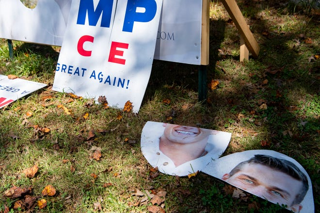 """A custom-made combination sign supporting Donald Trump for president and Madison Cawthorn for congress sits destroyed on the side of Sweeten Creek Road on Oct. 13, 2020. The owner of the sign, Jesse Moffitt, said it took him all day to build. """"I would never destroy a Biden sign just because I have a different opinion,"""" Moffitt said. """"It's their right to have their sign, it's their freedom of speech, but they can't just destroy my property because they have a difference of opinion."""" Moffitt plans to fix the sign and replace flags which he says keep getting stolen."""