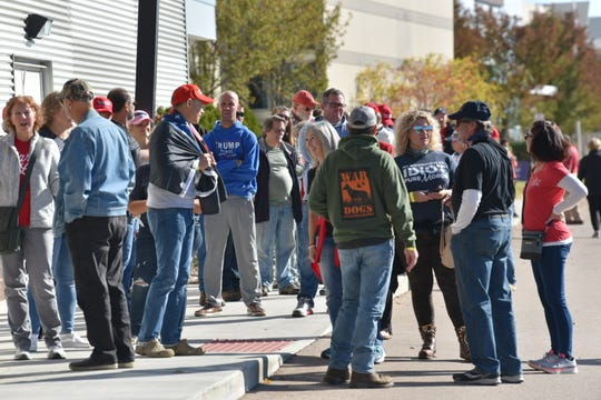 People wait in line outside the Suburban Collection Showplace in Novi, Tuesday, Oct. 13, 2020, before Eric Trump speaks.