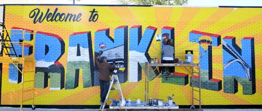 Artists Michael Cooper and Tara King paint Franklin's first public art mural on the Walk-In Urgent Care wall on Hillsboro Road in Franklin on Oct.  8, 2020.