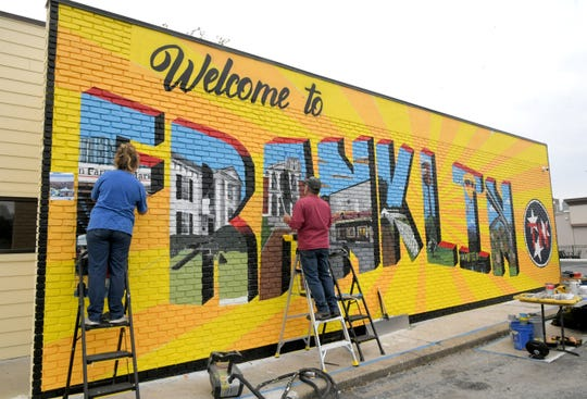 Artists Tara King and Michael Cooper paint Franklin's first public art mural on the Walk-In Urgent Care wall on Hillsboro Road in Franklin on Oct.  8, 2020.
