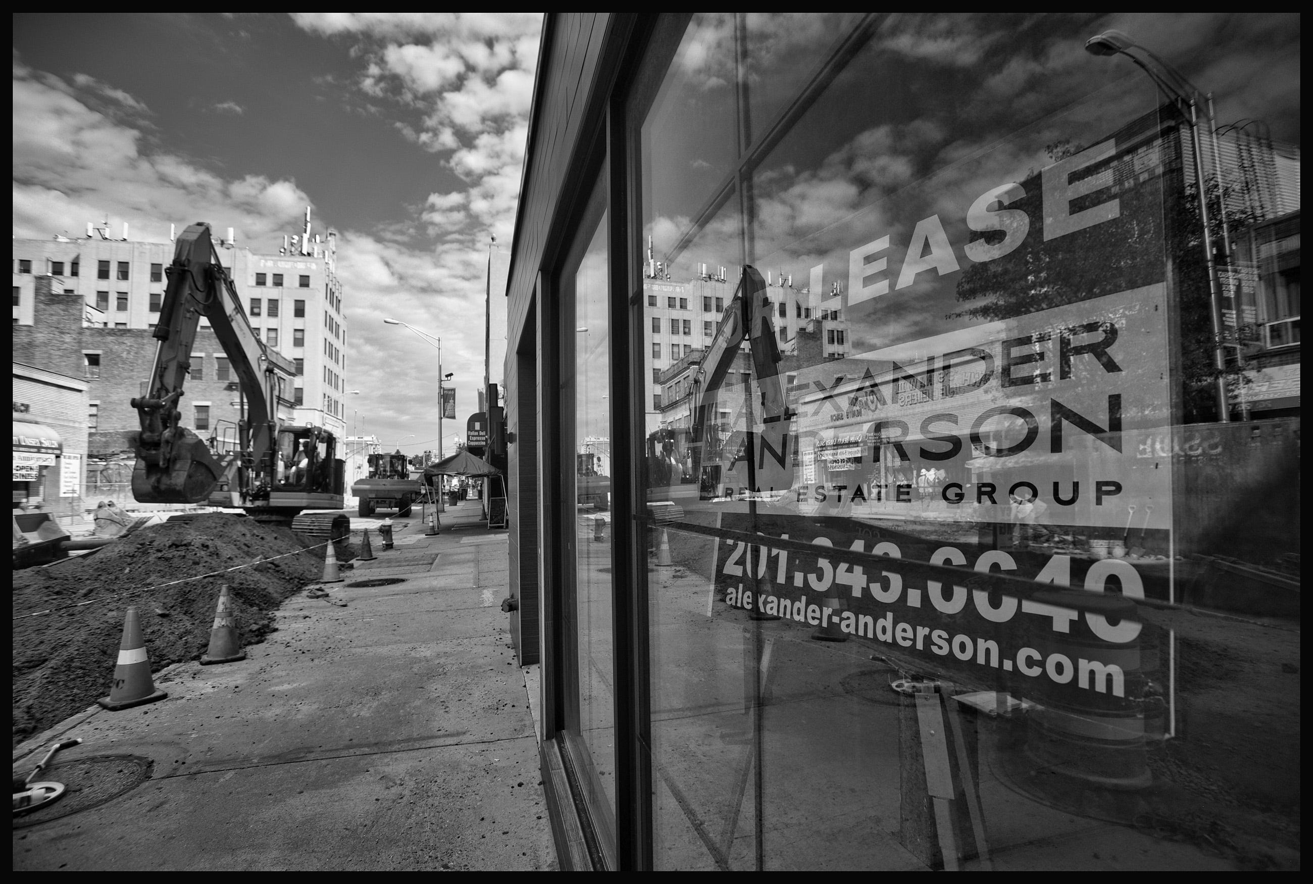 Construction continues in front of a commercial building with a for lease sign in the window along Main Street in Hackensack.
