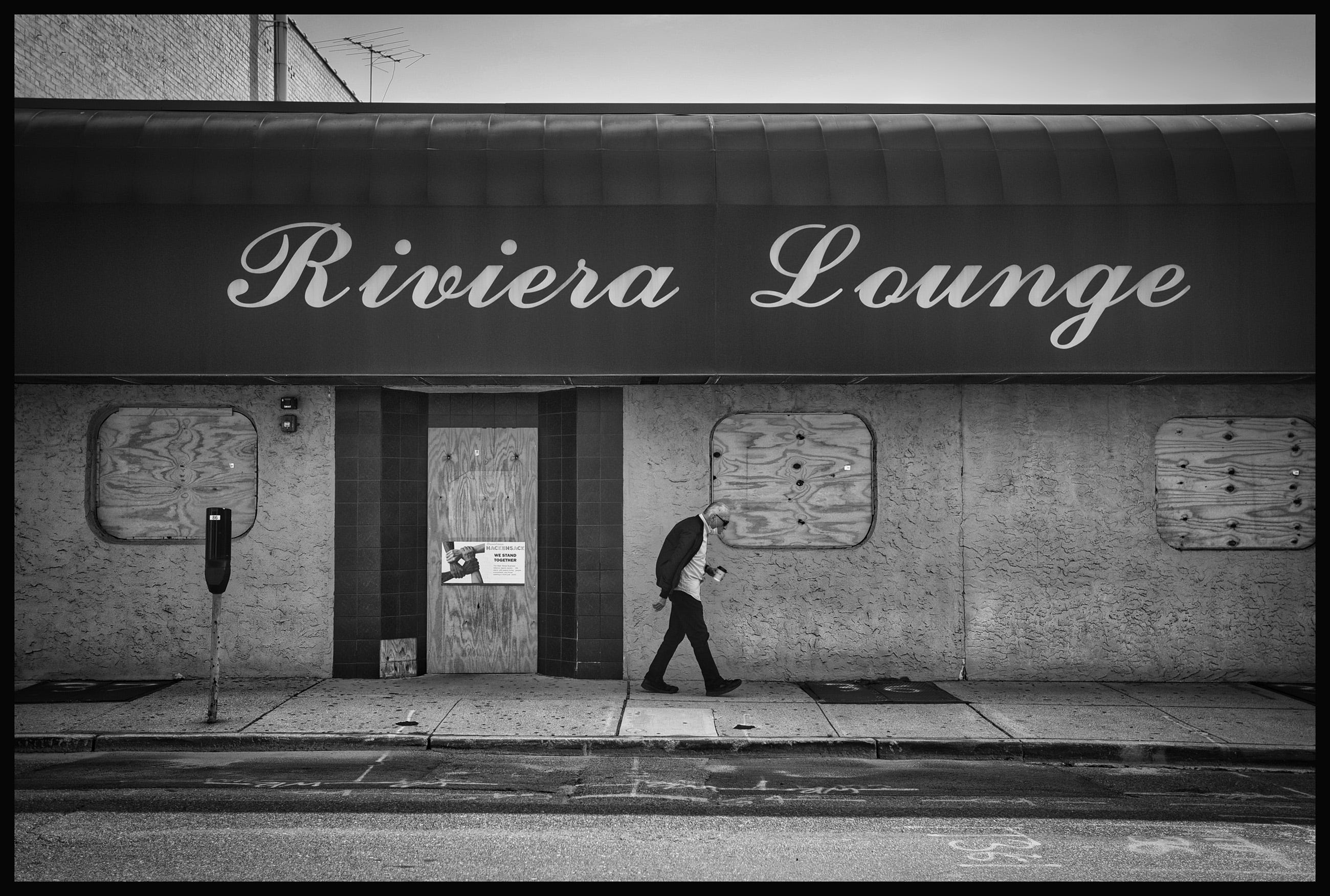A man walks past the closed Riviera Lounge located along Main Street in Hackensack, photographed on October 1,2020.